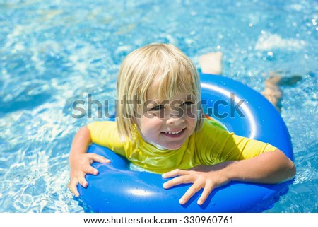 Happy little boy  with blue life ring has fun in the swimming pool - stock photo