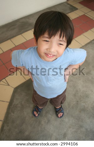 Happy little boy with blue t-shirt standing and looking up - stock photo