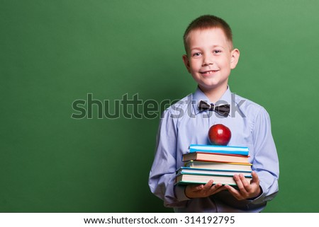 Happy little boy with books isolated on green background - stock photo