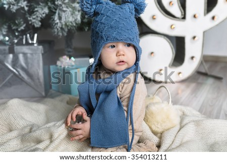 Happy little boy with fur headphones. under the Christmas tree - stock photo