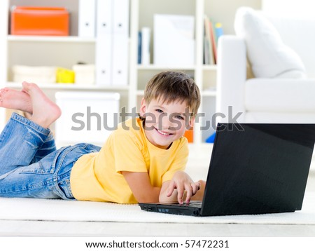 Happy little boy with laptop lying on the floor at home - indoors - stock photo