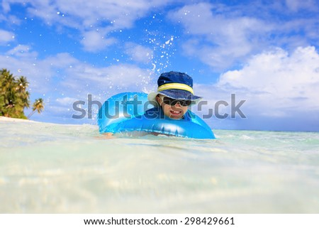 happy little boy with life ring has fun on tropical beach - stock photo