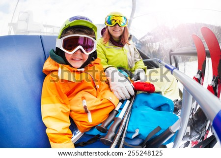 Happy little boy with mom, mountain ski chair lift - stock photo