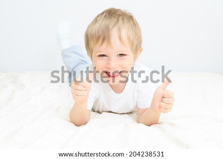 happy little boy with thumbs up on white background - stock photo