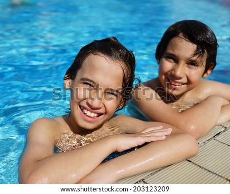Happy little boys enjoying relaxing and splashing in water - stock photo