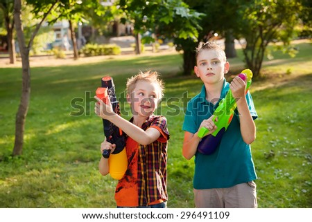 happy little boys playing with water guns - stock photo