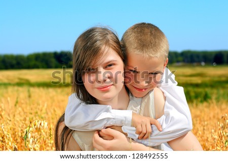 Happy little brother and sister portrait in the summer wheat field - stock photo