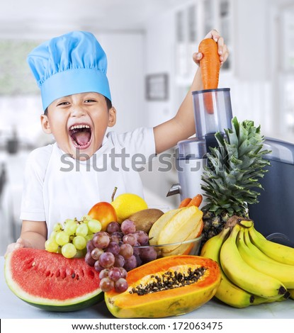 Happy little chef is making healthy fruit juice at home - stock photo