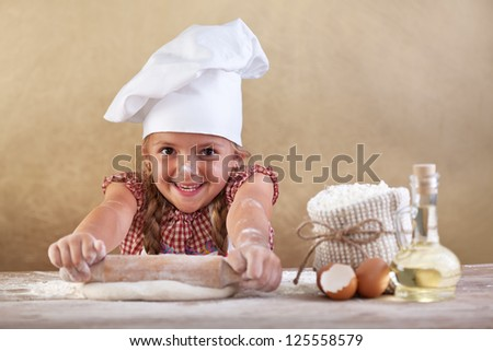 Happy little chef smeary with flour stretching the dough - stock photo
