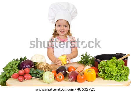 Happy little chef with vegetables preparing a healthy meal - stock photo