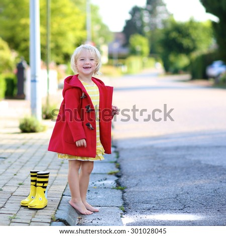 Happy little child, adorable blonde curly toddler girl wearing red duffle coat enjoying sun after rain running barefoot and jumping on the puddle on the street on a sunny autumn or spring day - stock photo