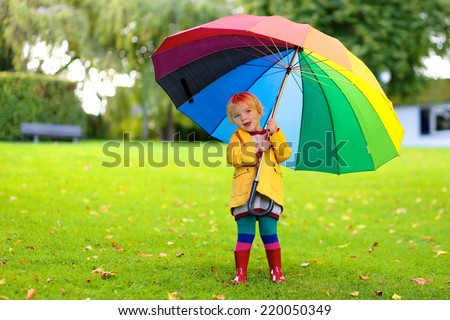Happy little child, adorable blonde curly toddler girl wearing yellow waterproof coat and red boots holding colorful umbrella playing in the garden or park on a sunny rainy warm early autumn day