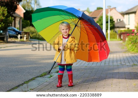 Happy little child, adorable blonde curly toddler girl wearing yellow waterproof coat and red boots holding colorful umbrella walking on street in city or village on sunny rainy warm early autumn day - stock photo