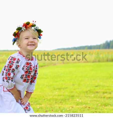 Happy little child, adorable blonde toddler girl dressed in national Ukrainian costume wearing wreath of flowers, peacefully playing in beautiful field in East of Ukraine - make love not war concept - stock photo