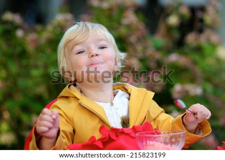 Happy little child, adorable blonde toddler girl, eating delicious ice cream sitting comfortable in cozy outdoors cafe wrapped in warm red plaid on sunny autumn or winter day - stock photo