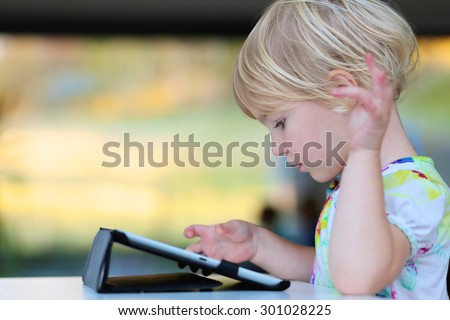 Happy little child, adorable blonde toddler girl enjoying modern generation technologies playing indoors using tablet pc with touchscreen. - stock photo