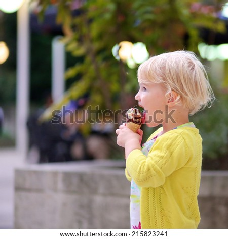 Happy little child, adorable blonde toddler girl in beautiful dress, walking on crowded touristic street in the center of the city eating ice-cream on a sunny summer evening - stock photo
