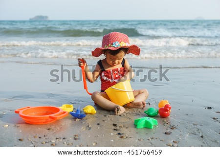 Happy little child, adorable blonde toddler girl in colorful swimsuit playing on the beach with toys - stock photo