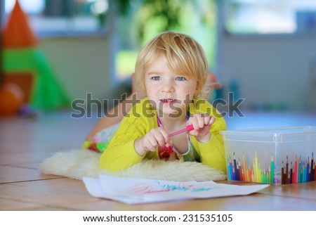 Happy little child, adorable blonde toddler girl lying comfortable on tiles floor on warm lambskin drawing on paper with colorful pens on sunny day - stock photo