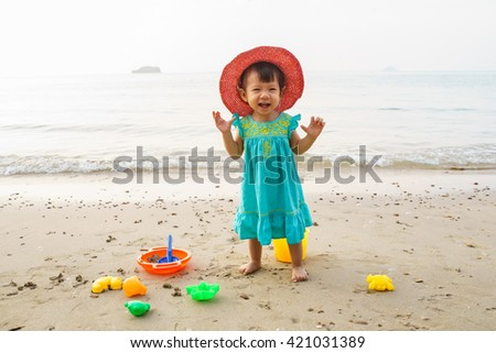 Happy little child, adorable blonde toddler girl playing on the beach with toys - stock photo
