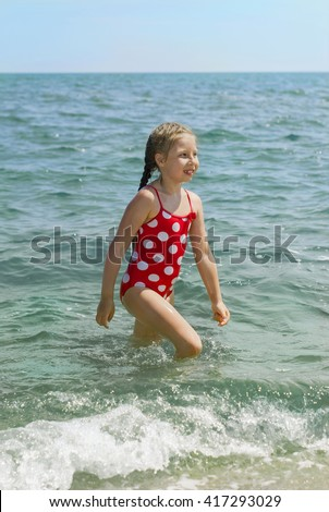 Happy little child, adorable blonde toddler girl wearing colorful swimsuit on the beach Azov Sea out of the water after bathing - stock photo