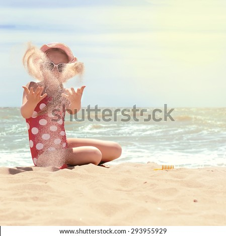 Happy little child, adorable blonde toddler girl wearing colorful swimsuit playing on the beach Azov Sea making ice cream from sand using plastic toys, selective focus, toned photo - stock photo