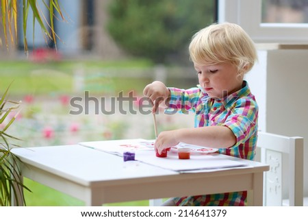 Happy little child, adorable blonde toddler preschooler girl, drawing on paper with colorful paint and brush sitting indoors at white table at home or kindergarten next to a big window - stock photo