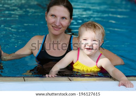 Happy little child, adorable toddler girl, having fun in the swimming pool together with her young mother - stock photo