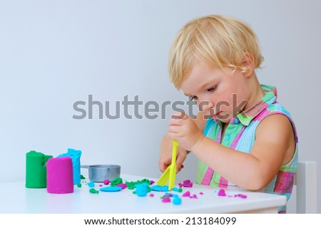 Happy little child, adorable toddler preschooler girl creating using  dough, colorful modeling compound - stock photo