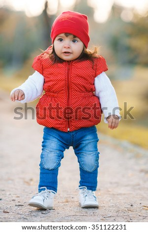 happy little child, baby girl laughing and playing in the autumn on the nature walk outdoors. happy little girl have fun playing with fallen golden leaves
