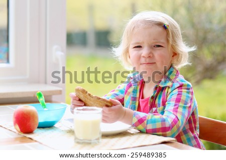 Happy little child, blonde curly toddler girl, enjoying healthy breakfast eating yogurt, sandwich and apple and drinking milk sitting in at bright sunny kitchen next to big garden view window - stock photo