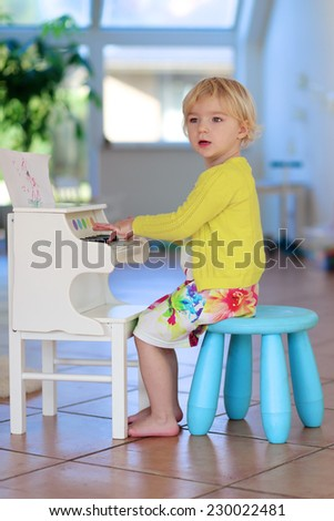 Happy little child, blonde curly toddler girl having fun playing piano toy sitting on small chair standing on the tiles floor in bright sunny room with big window - stock photo