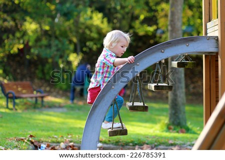 Happy little child, blonde curly toddler girl in bright casual outfit, having fun climbing brave on the playground on a sunny day - stock photo