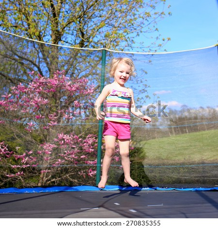 Happy little child, blonde curly toddler girl jumping on trampoline in the garden at the backyard of the house on a sunny summer day - stock photo