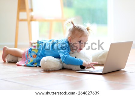 Happy little child, blonde toddler girl enjoying modern technologies playing indoors using laptop pc lying cozy on tiles floor - computers generation, education, networking and communication concept - stock photo