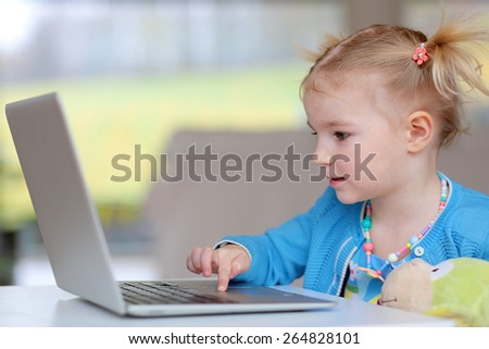 Happy little child, blonde toddler girl, enjoying modern technologies playing indoors using laptop pc sitting at white table - computers generation, education, networking and communication concept - stock photo