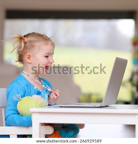 Happy little child, blonde toddler girl enjoying modern technologies playing indoors using laptop pc sitting at white table - computers generation, education, networking and communication concept - stock photo