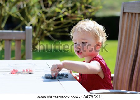 Happy little child, cute blonde toddler girl in beautiful dress snacking outdoors in the garden at the backyard of the house sitting on a wooden teak chair on a sunny summer day eating berries - stock photo