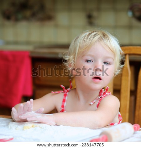 Happy little child, cute blonde toddler girl, sitting at the table in classic traditional wooden kitchen making delicious sweet gingerbread xmas cookies - stock photo