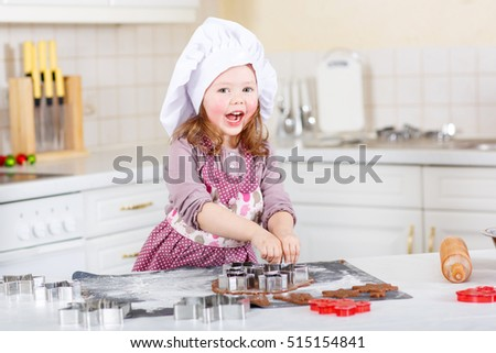 Happy little child, cute kid girl, sitting at the table in domestic kitchen making delicious sweet gingerbread xmas cookies. Kitchen decorated for Christmas holiday. Girl helping and having fun