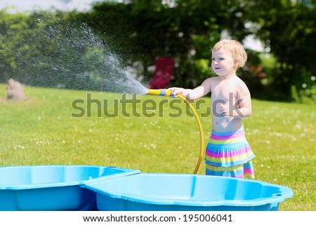 Happy little child, funny blonde toddler girl playing with water hose outdoors in the garden at the backyard of the house on a hot sunny summer day - stock photo