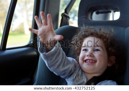 Happy  little  child (girl age 2) travel in a car sit during family holiday vacation. - stock photo