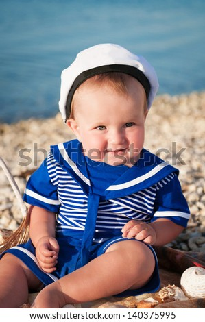 happy little child in a suit of the seaman smiling and having fun on the sea. adorable cute babe playing and resting on nature. trendy blond funny child on nature enjoying the sun in park and posing - stock photo