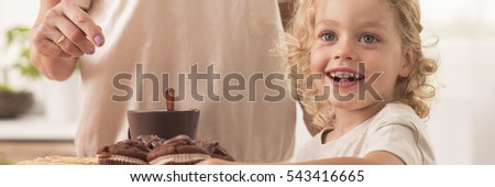 Happy little child in front of chocolate muffins, with grandma in the background