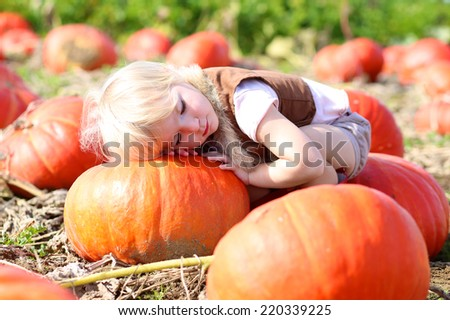 Happy little child, laughing cute toddler girl in casual outfit and red rubber boots, enjoying nature playing outdoors helping to harvest bio pumpkins growing in organic field on sunny autumn day