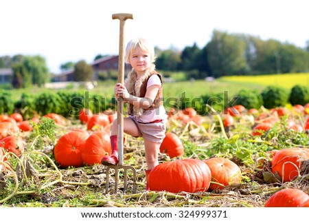 Happy little child, laughing cute toddler girl in casual outfit and red rubber boots, enjoying nature playing outdoors helping to harvest bio pumpkins growing in organic field on sunny autumn day - stock photo