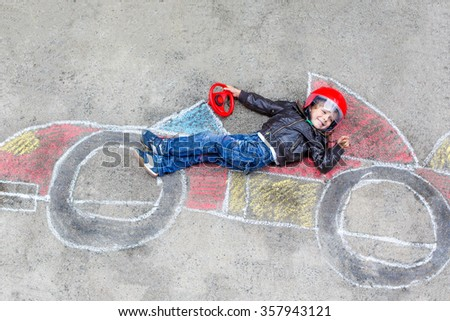 Happy little child of four years having fun with race car picture drawing with colorful chalks. Creative leisure for children outdoors in summer - stock photo