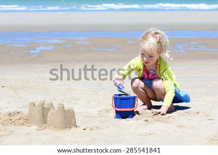 Happy little child on the beach. Cute toddler girl enjoying summer vacation at the North sea building sand castles and playing with plastic toys.