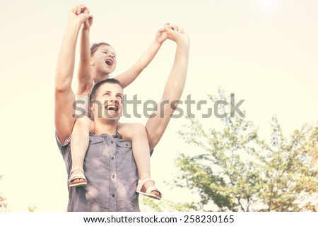Happy little child on uncle shoulders outside in nature enjoying beautiful day - stock photo