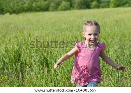 Happy little child running in the field over green grass background - stock photo